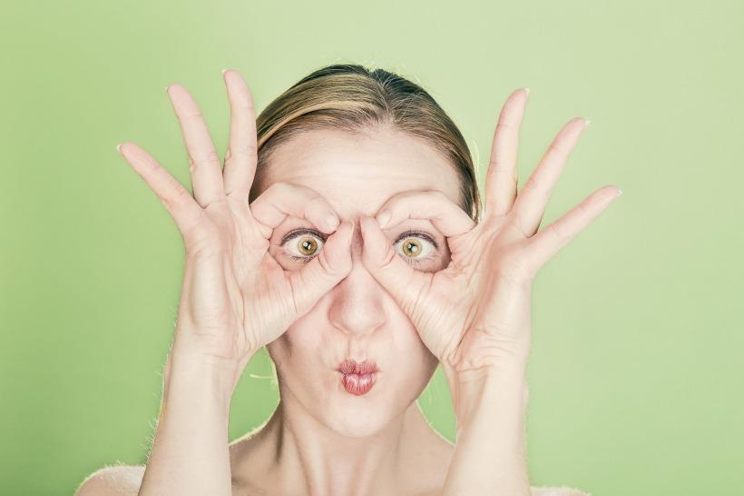 Femme avec les doigts placées autour des yeux comme des jumelles