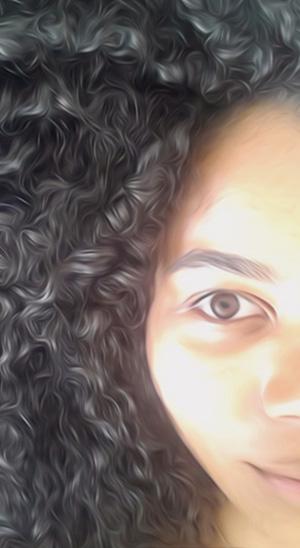 Mégane auteur du blog Stay happy. Be curly. Portrait demi-visage jeune fille métisse aux cheveux bouclés