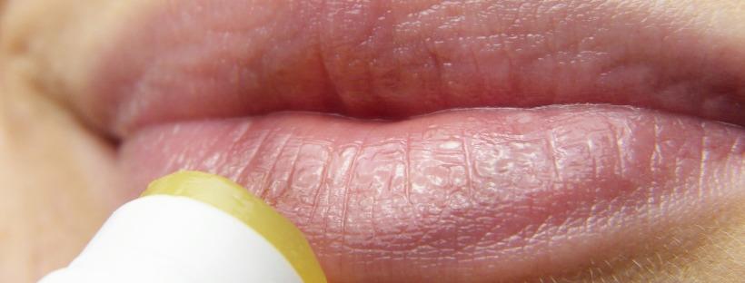 Lèvres de femme avec un baume en train d'être appliqué