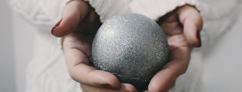 Mains jointes tenant une boule de Noël