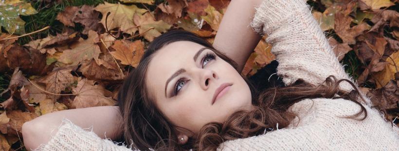 Femme allongée sur un tapis de feuille en train de regarder le ciel