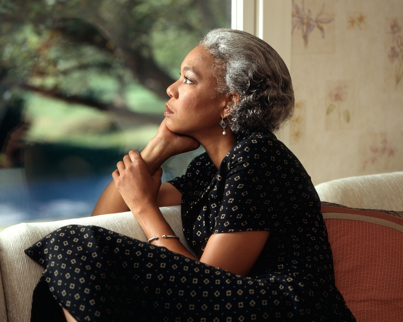 Femme en train de réflechir en regardant au loin