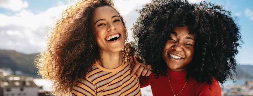 Femmes aux cheveux bouclés souriant