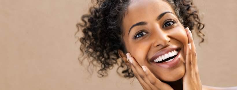 Femme souriant et se touchant la peau