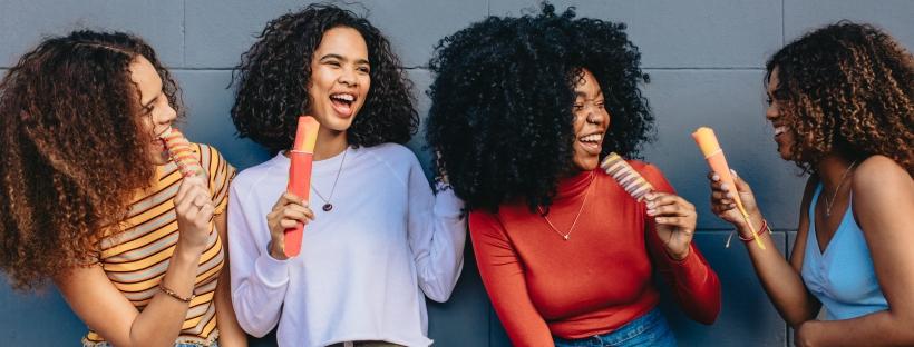 Femmes aux cheveux bouclés rigolant